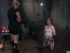 Nerdy brunette Kristine is playing BDSM games with Maitresse Madeline in a basement. The dominatrix beats and humiliates Kristine and then pours wax on her body and drills her pussy with a strapon.