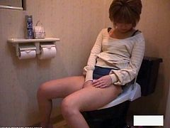 Amateur Asian slut toys hairy pussy in the toilet. She's lost in her horny world with her favorite toy for all to see.