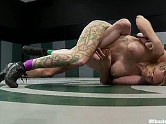 Tattooed blonde chick and nasty brunette wrestle in Ultimate Surrender tournament. The blonde wins a fight. So, she toys the brunette in her wet vagina.