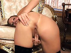 Carmen Gemini with shaved bush has fire in her eyes as she fucks herself with sex toy