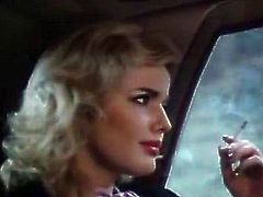 Stunningly hot blonde lady in fine clothes talks on the telephone with some guy and smokes her long cigarettes seductively moving her lips.