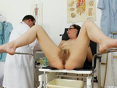 Saggy whore Slaven is at her gynecologist. The doc putted her to take a sit on the special table and then she spread her legs. He putted some lube on her hairy pussy and then asked her to stretch it with a dildo. Now that her pussy is roomy enough, he inserts a speculum to check it out on the inside!