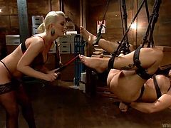Tied hanged and ball gagged Syren endures what her blonde mistress give her. She hangs there as the whore spanks that shaved, delicious pussy and her feet. Looks like the blonde takes her time and enjoys what she does to Syren