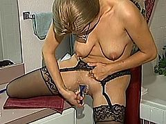 Kinky amateur chick with hanging boobs shaves her pussy in a bathroom. Then she gets toyed with a vibrator by some dude.