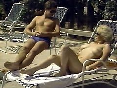 Lovely blonde milfie with big natural tits and huge butt takes sunbath totally naked. One cocky stud eats her meaty shaved pussy and fucks her missionary style over the poolside.