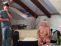 This blonde granny with big saggy tits is sitting naked on the couch when her daughter's partner walks in. He opens a bottle of wine for her and fucks her doggy style.