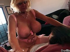 This sex-starved bitch with huge juicy melons has a never ending sex drive. She climbs on top of this young stud's cock and rides him passionately in cowgirl position. The way her big tits bounce up and down guarantee his dick won't go limp.