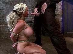 Blonde chick with huge boobs gets tied up by a couple. Holly gives a blowjob to her master and gets toyed with a strap-on by the mistress.