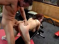 Lustful redhead chick stands on her knees and gives a titjob in a gym. Later on she gets her ass and pussy fucked by muscled guy.