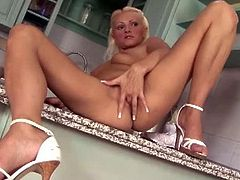 Chrisy Bloom is a slender older woman with blonde hair. She poses in her kitchen and fingers herself on the kitchen's floor. She doesn't care where she is, she's enjoying the fingering.