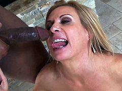 A horny skanky-ass MILF with big-ass motherfuckin' tits sucks on a hard black cock and gets it shoved balls deep into her snatch!