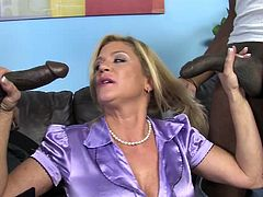 Witness this video where a blonde MILF, with gigantic tits wearing a miniskirt, serves free handjobs and goes hardcore with two black guys.