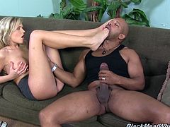 This cute blonde girl wraps her feet around this black guy's thick cock and gives him a footjob until he cums all over toes.