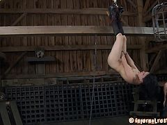 Juliette has her head locked in a metal cage when her master fucks her with a stick. Then, he ties up her legs and suspends her. He fucks her throat while hanging like that.