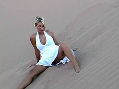Sweet blonde babe in a white dress makes a solo show in the heart of a desert. She lies down on the sand. Her dress is flutters so that you can see her ass and pussy.