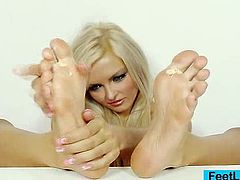 Incredible handsome blond sits down takes off her socks to oil her splendid feet and sole. After that, she strokes a plastic cock with her foot