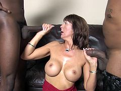 Slim cougar with fake boobs sucks two big black cocks standing on her knees. Then Desi Foxx gets rammed in her wet pussy.