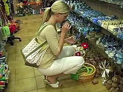 Curvaceous blonde girl shows her natural boobs around the corner. Then she goes to a shop to buy some stuff.