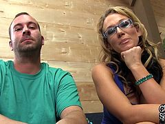 Blonde MILF in glasses shows her big boobs and also rubs a pussy. Then she lies down on a sofa and gets her face cum covered in a backstage video.