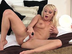 Blonde girl shows off while deep pounding her cunt with a stiff toy