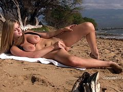 Curvy blonde Danielle wearing a bikini is having a good time at a beach. She walks along the shore and then demonstrates her big natural tits and pleases herself with fingering.