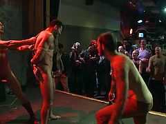 In this gay bar everybody's having fun, except Billy. Billy can't enjoy himself too much because he's being tied up and offered to the public. When he's brought on the stage, completely naked and all tied, the boys go crazy! They cheer him and then begin to fuck the hot brunette sex slave's mouth.