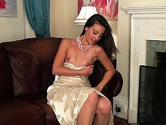 A beautiful brunette babe takes off her evening dress. So, she poses for a camera in stockings and lingerie. Lorena plays with her pussy sitting on a floor.