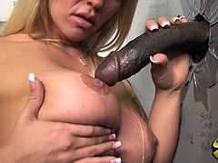 Click to watch this blonde cougar, with giant knockers wearing a miniskirt, while she gets fucked by a big black cock coming from a gloryhole.