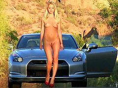 Sexy Casy makes a stop outside of town and gets out of her sport car. This blonde girl takes off her dress. There is nobody near, so she walks naked along the empty road in the mountains.