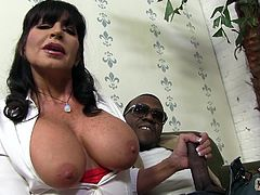 Tara Holiday unbuttons a shirt to show her huge boobs. She talks on camera and gives a handjob to Black dude at the same time.