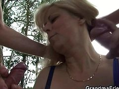 Milena and her two male friends are out in nature. They enjoy the landscape and the wilderness until grandma wants to enjoy something else. Our blonde granny soon goes wild with these guys and greedily grabs their cocks. She stays on her knees and sucks them both with a lot of passion. What a fucking whore!
