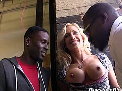 Get wild watching this blonde cougar, with fake boobs and long hair, while she goes wild with two black guys in a backstage video.