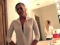 Alison Angel poses in front of a mirror in her thong
