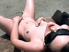 Sasha Grey is sitting on a bench situated on the roof. She takes her black attire off slowly and begins to rub her trimmed pussy while the sun tans her body.