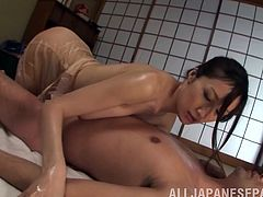 A stunning Asian MILF takes off her clothes and gets oiled up. She gives an amazing massage and pleases a guy with her feet.