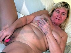 Chubby granny mature is playing on the couch with her pink vibrator to make her pussy wet. A cute young girl used a big strapon to penetrate that old fat cunt.