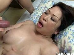 Make sure you see this! An Asian brunette, with a nice ass and big knockers, while she gets badly screwed by a horny dude over a bed.
