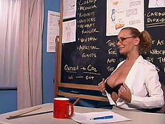 Press play to watch a blonde teacher, with big boobs wearing sexy glasses, while she goes hardcore with two coeds in her classroom.