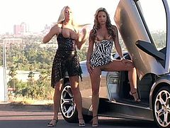Alison Angel and another girl pose for a camera near a silver Lamborghini. These babes shows their sexy legs and big boobs.