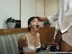 This Asian babe has her hands tied up and a mouth-opening device on. Her master fucks her face and cums inside her mouth. Her saliva and the sperm drip out.
