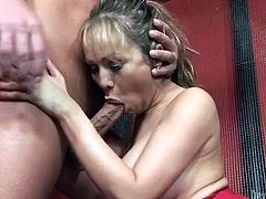 Slutty blonde shemale with big fake boobs is sitting topless in front of her coach. She takes his dick in her mouth pumping intensively.