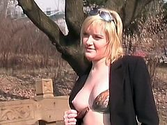 Sexy milf shows off her boobies outdoors