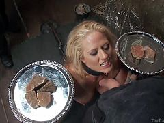 This blonde slave has to follow directions and be obedient. Her masters are very cruel to her. Watch as they make her kneel on the ground and suck cock while balancing two trays in her hands. She better not drop them!