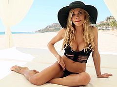 Hot blonde Dani Mathers is having a photo shoot on a beach. The blonde poses for the cam in her swimsuit, then takes it off and flashes her big fake tits for the cam.