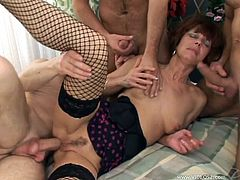 Have a good time watching this short haired mature lady, with natural knockers wearing fishnet stockings, while she goes hardcore with too many pipes.