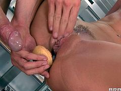 A pretty redhead with long hair, big tits and an awesome body enjoys a hardcore missionary style fuck in a restaurant kitchen.