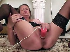 Kashmir was dusting right where her favorite vibrator was. She took it out and then started using it while sitting on the floor. She toys that mature cunt hard.
