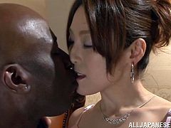 Horny Japanese bitch, wearing lingerie and stockings, spreads her legs wide apart and lets a black guy play with her pus