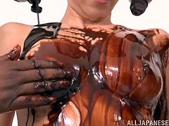 Mao is a sexy Japanese girl strips off her clothes and lets these two guys cover her fine body in chocolate then jizz all over her.