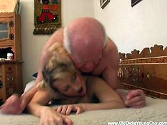 A sizzling girl with long blonde hair, massive tits and a nice body enjoys licking and sucking an older man's cock in his bedroom.